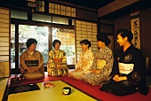 Japanese women kneeling on the floor beginning tea ceremony