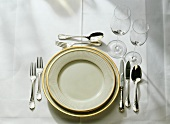 Table setting: gold-rim plates, cutlery, fish cutlery, glasses