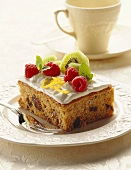 A piece of spice cake with white icing, raspberries & kiwi fruit