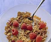 A dish of wholemeal cornflakes, raspberries and milk