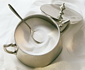 A silver sugar bowl and spoon on pile of sugar