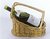 A bottle of red wine in a wine basket