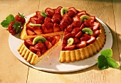 A strawberry flan with kiwi pieces on cake plate