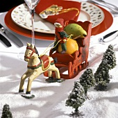 A table setting & wooden horse and sleigh (sledging party)