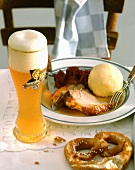 Roast pork with red cabbage & dumpling, weissbier beside it