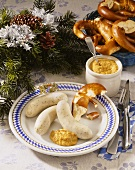 Plate with white sausages, pretzel and sweet mustard