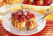 Strawberry tartlet with vanilla cream, piece on fork