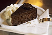 A piece of Sacher torte with cream in Hotel Sacher in Vienna