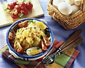 Potato salad with fried bacon cubes, eggs & tomatoes