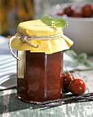 Cherry jam in a jar, with fresh cherries beside it