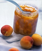 Apricot jam in a jar, decoration: peaches and sugar