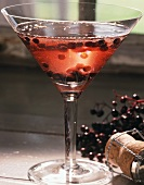 Sparkling wine with elderberries in stemmed glass