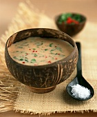 Tamarind & coconut soup with coriander & mint in wooden bowl