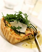 Bacon quiche with rocket and Parmesan on plate