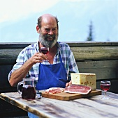 Farmer having afternoon snack (Jause) with bacon, cheese & wine