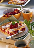 A piece of tray-baked redcurrant cake on a plate