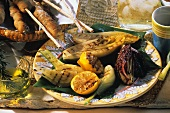 Grilled vegetables and oranges, with bread stick