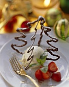 Chocolate fir tree on vanilla ice cream with strawberries