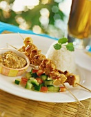 Satay kebabs with rice, salad and peanut sauce