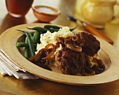 Rissoles with mashed potato, beans and onion sauce
