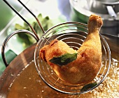 Chicken leg with sage being lifted out of deep-frying fat