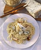 Spaghetti with pearl onions, turkey roll and gorgonzola