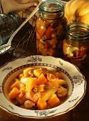 Pumpkin stew with smoked pork rib on plate, decor: jars
