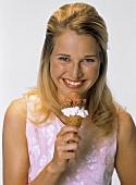 Junge blonde Frau hält Eistüte in der Hand