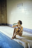 A Woman Drinking Water by the Pool