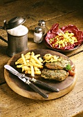 Herbed steak with onions and chips on wooden platter