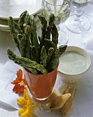 Fresh green asparagus stalks with herb dip