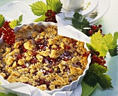 Redcurrant crumble cake with almonds in baking tin