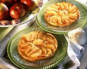Two tartes tatins on glass plates