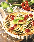 Courgette and tomato quiche garnished with basil