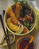 Fish snacks with vegetables, rice & chili sauce in bowl