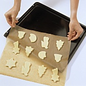 Placing cut out biscuits on to baking sheet