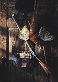 Still life with dead pheasant, leather bag and rifle