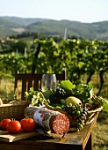 Table with salami, tomatoes, grapes in front of Tuscan vineyard