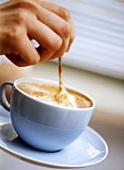 Cappuccino in hellblauer Tasse umrühren