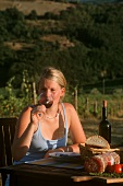 Young woman drinking wine in a Tuscan vineyard