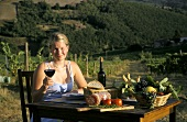 Laid table in Chianti vineyard: woman holding glass of wine