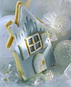 Blaues Häuschen aus Mürbteig, umgeben von Weihnachtskugeln