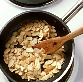 Toasting flaked almonds in a frying pan