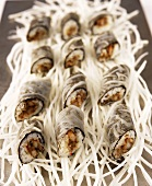 Sushi rolls in rice paper on radish strips