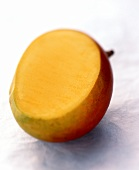 A mango, cut into, on pale blue background