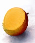 Eine angeschnittene Mango auf hellblauem Untergrund