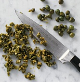Finely chopping capers