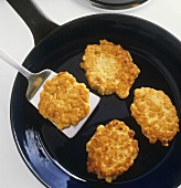 Frying corn cakes in a frying pan
