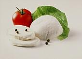 Still life with mozzarella, tomato & lettuce leaf