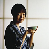 Asian woman holding bowl of tea
